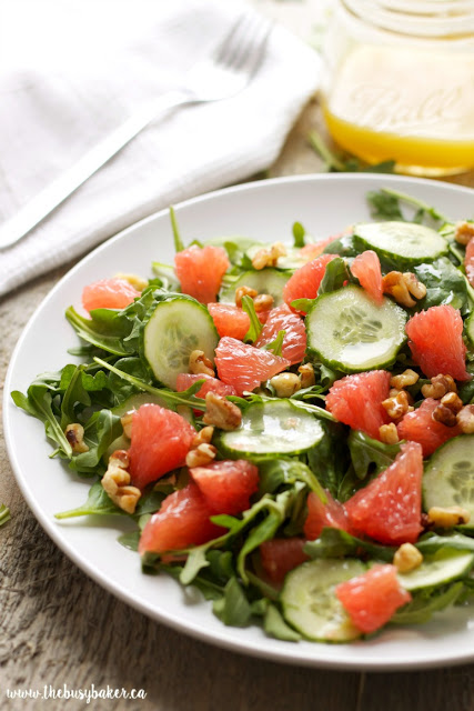 plate of grapefruit salad made with healthy greens, cucumbers, and chopped walnuts