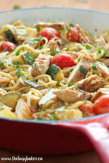chicken and pasta primavera in a red skillet