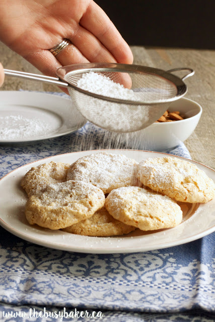 dusting powdered sugar over Italian almond cookies (amaretti cookies)