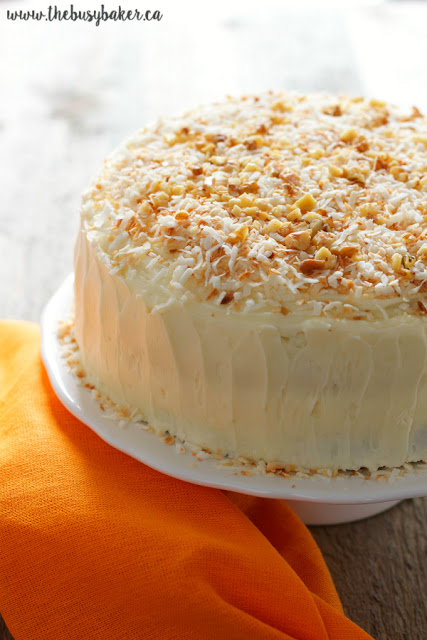 homemade carrot cake with cream cheese frosting topped with chopped walnuts