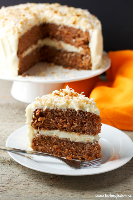 slice of classic homemade carrot cake on a plate with the rest of the carrot cake on a stand behind it.