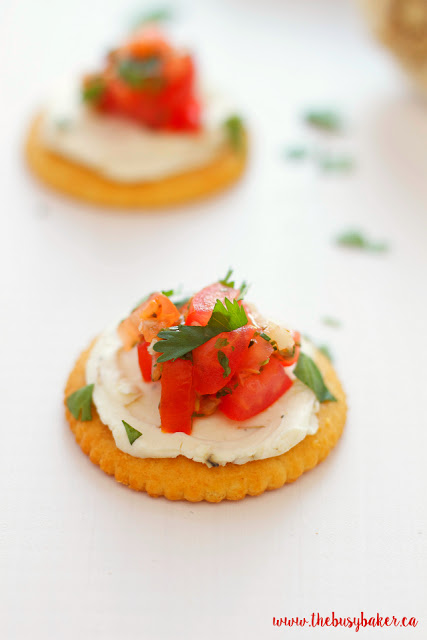 buttery cracker topped with garlic cream cheese spread, tomatoes and fresh basil