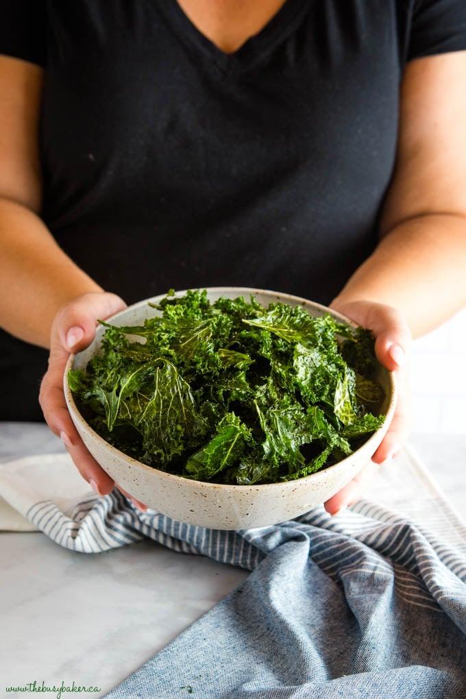 hands holding bowl of kale chips