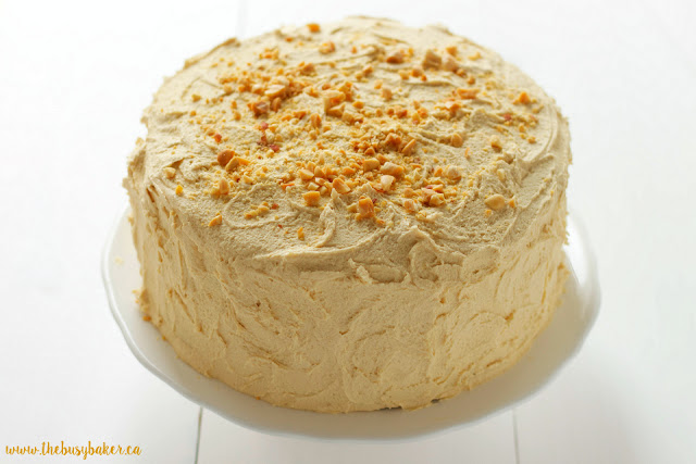 homemade banana cake topped with peanut butter frosting and crushed roasted peanuts