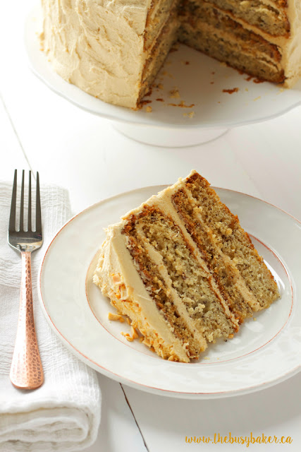 dessert plate holding a slice of banana layer cake with fluffy peanut butter frosting