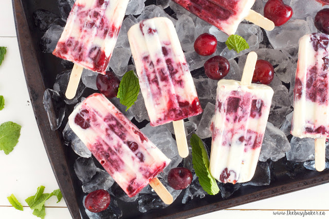 a sheet pan full of ice holds homemade Cherry Cheesecake Popsicles