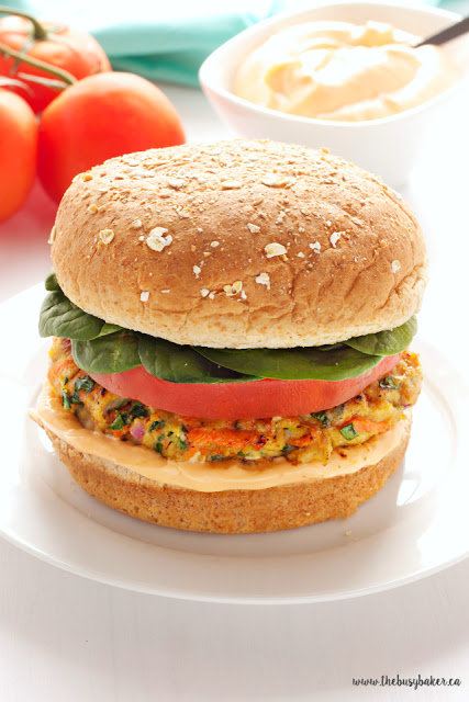 a healthy ground turkey burger topped with baby spinach, tomato, and sriracha mayo