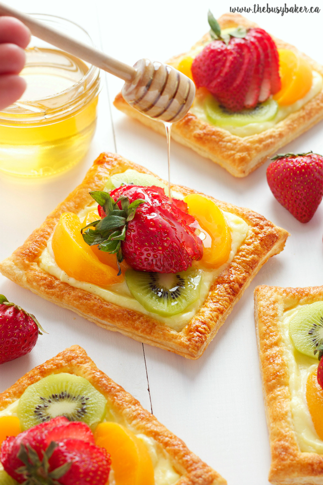 honey being drizzled over individual fresh fruit tarts