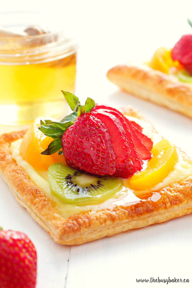 close up image of a vanilla bean custard fruit tart with honey glazed fruit on top