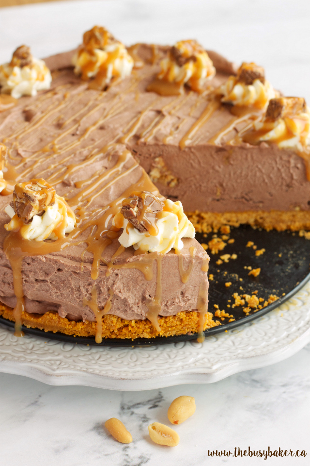 This Easy No Bake Snickers Cheesecake is the perfect easy to make decadent dessert! Recipe from www.thebusybaker.ca