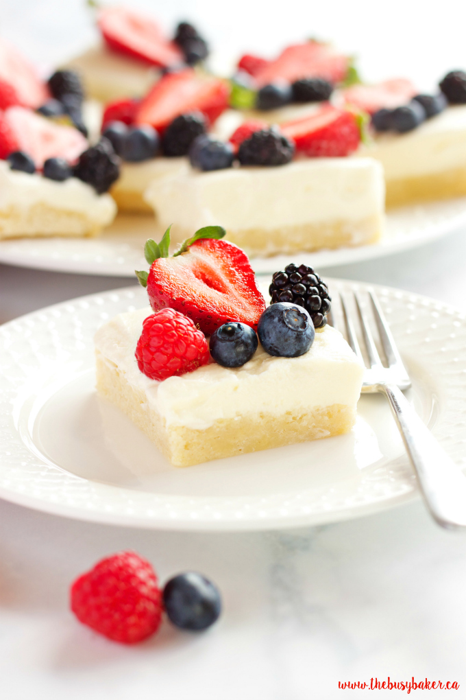 These Berry Cheesecake Sugar Cookie Bars make the perfect dessert for spring and summer featuring a cookie base, creamy cheesecake and fresh berries! Recipe from thebusybaker.ca!