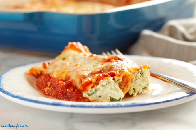 This Baked Ricotta and Spinach Cannelloni is made with three delicious cheeses and it's the perfect easy comfort food recipe that's also vegetarian! It's a pasta lover's dream recipe! Recipe from thebusybaker.ca!