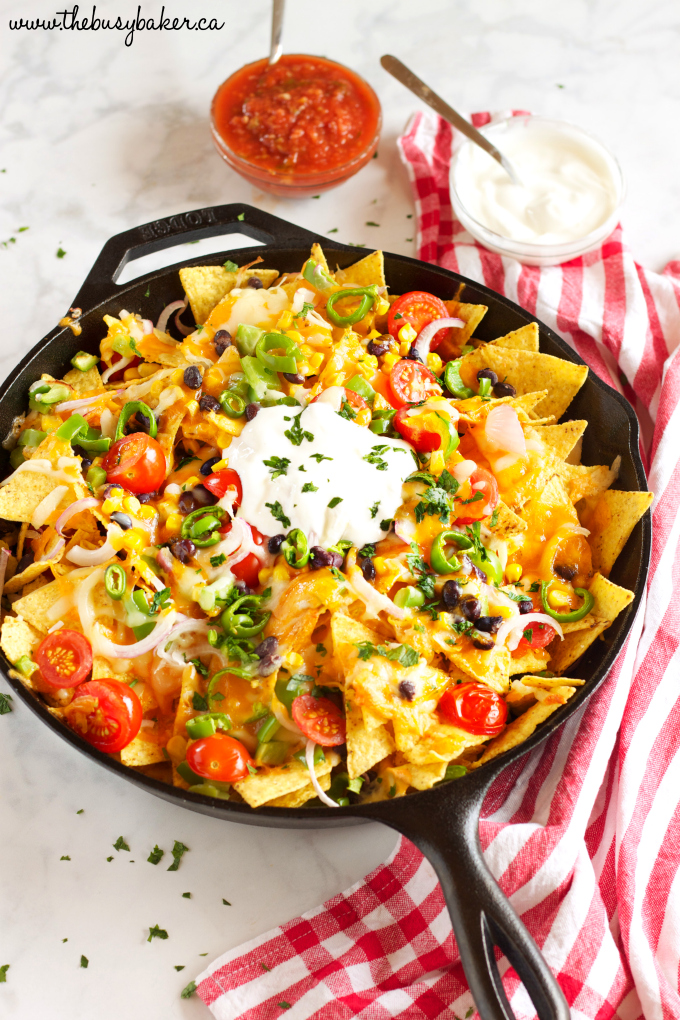 Healthy Vegetarian Nachos with corn, jalapenos, tomatoes, black beans, salsa and sour cream