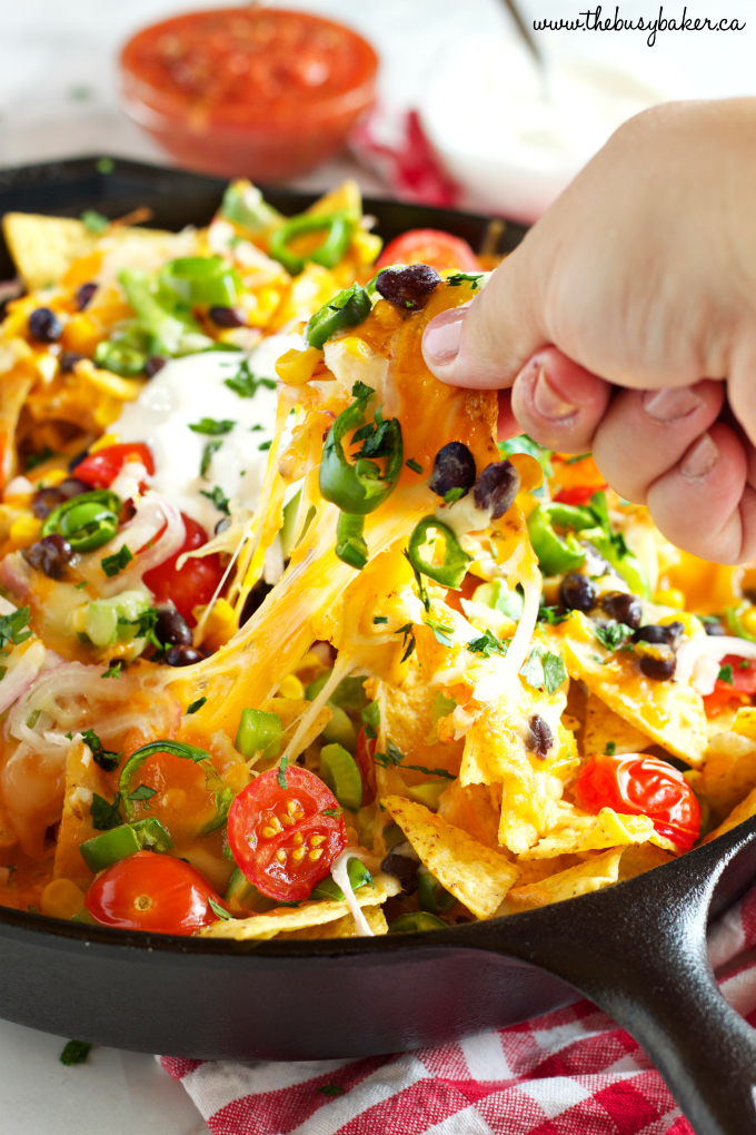 Vegetarian Nachos with stretchy cheese in skillet