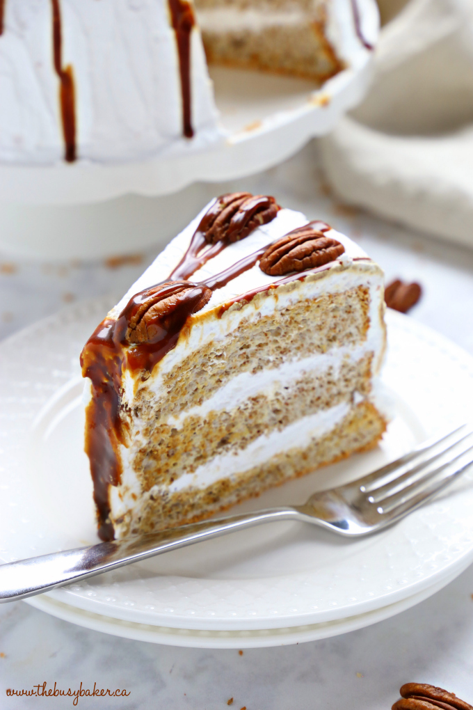 This Classic Caramel Pecan Schmoo Torte is a delicious and classically Canadian layer cake with a pecan-flavoured Angel Food Cake base, fluffy whipped cream frosting, and homemade caramel sauce! It's sweet and decadent and makes the perfect impressive dessert! Recipe from thebusybaker.ca! #schmootorte #canadiancake #caramelpecancake