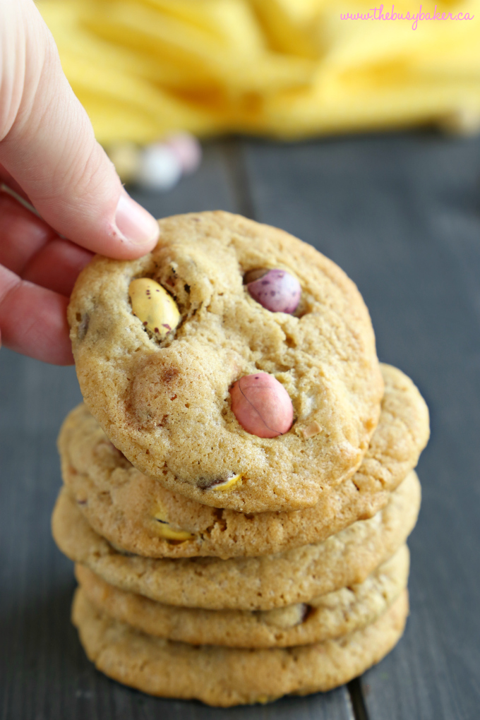 These Mini Eggs Chocolate Chip Cookies are the perfect easy snack or dessert for Easter! Made with the perfect soft and chewy chocolate chip cookie dough and stuffed with delicious candy-coated Mini Eggs, these cookies are beautiful, colorful, and perfect for Spring! Recipe from thebusybaker.ca! #minieggsdessert #minieggscookies #easyeasterdessert