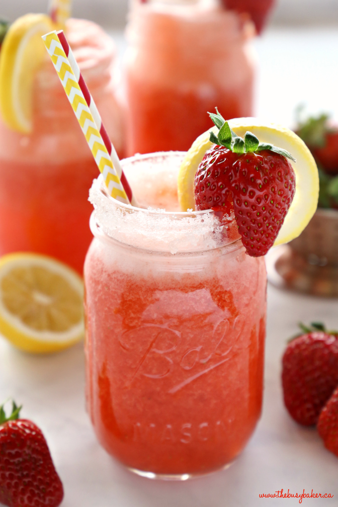 Healthy Strawberry Lemonade in mason jar with sugar rim and strawberries