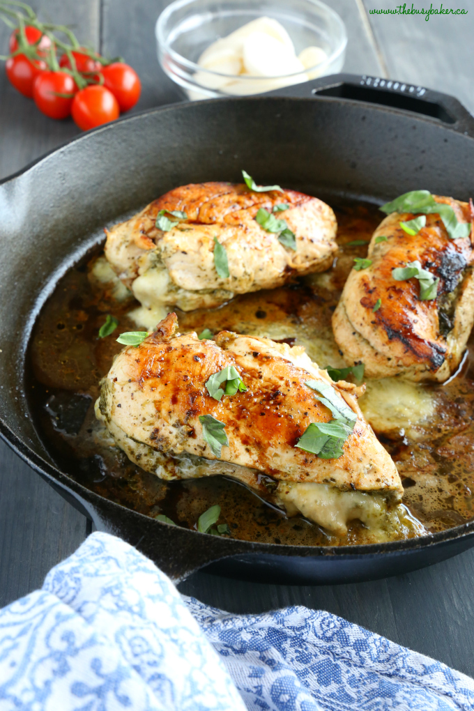 Pesto Caprese Chicken in skillet with basil and blue kitchen towel