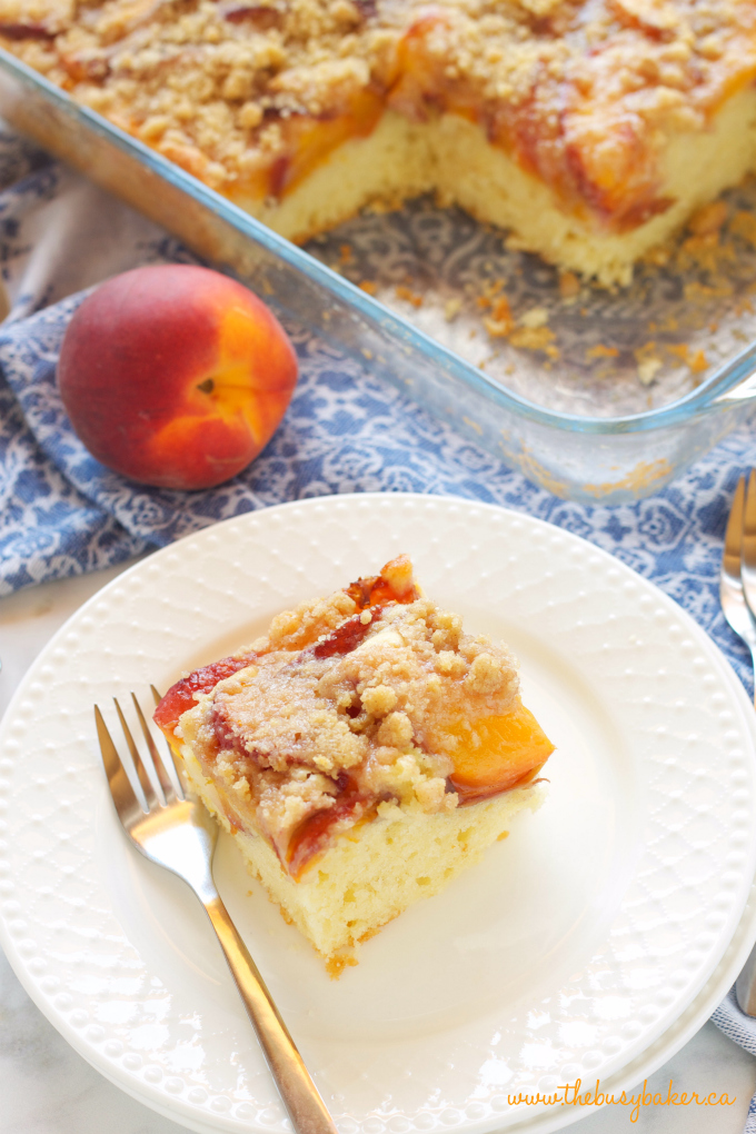 Peach Streusel Cake with blue fabric and fresh peach