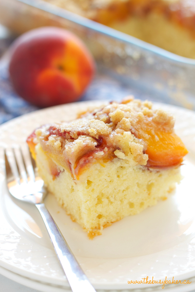 Peach Streusel Cake on white plate with fresh peach