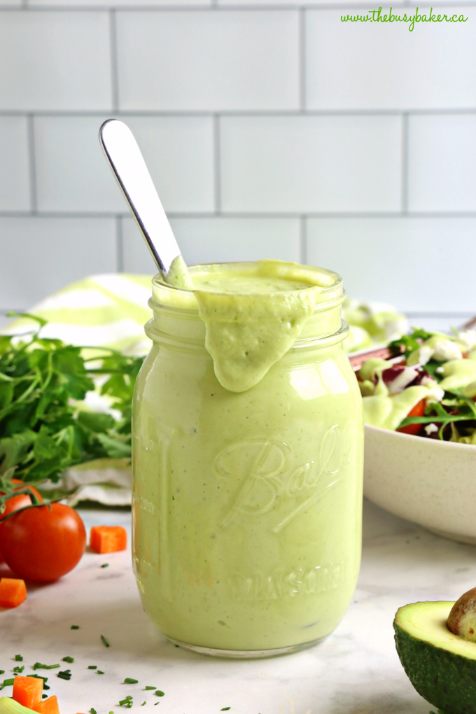 Healthy Creamy Avocado Ranch Salad Dressing in mason jar with salad and tomatoes