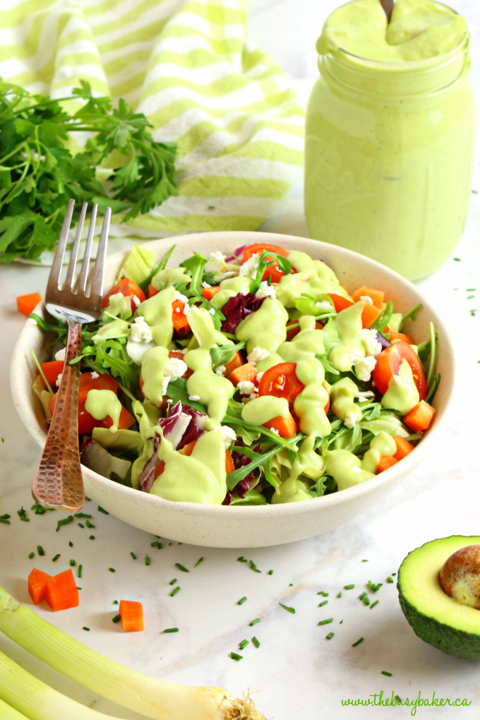 Healthy Creamy Avocado Ranch Salad Dressing on salad with avocado and herbs