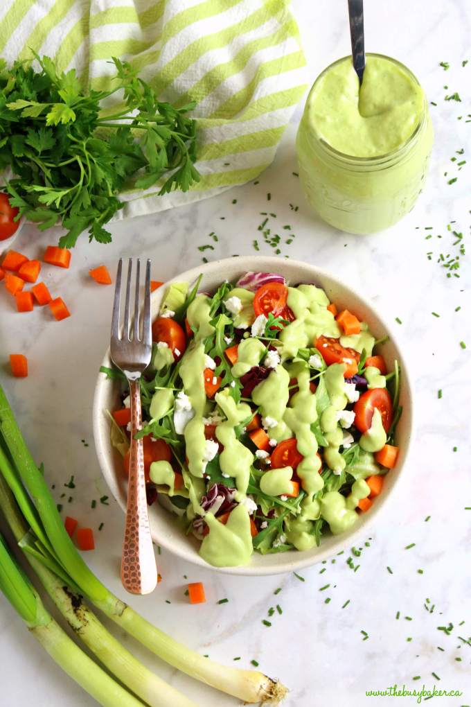 Healthy Creamy Avocado Ranch Dressing on garden salad with herbs and green onions