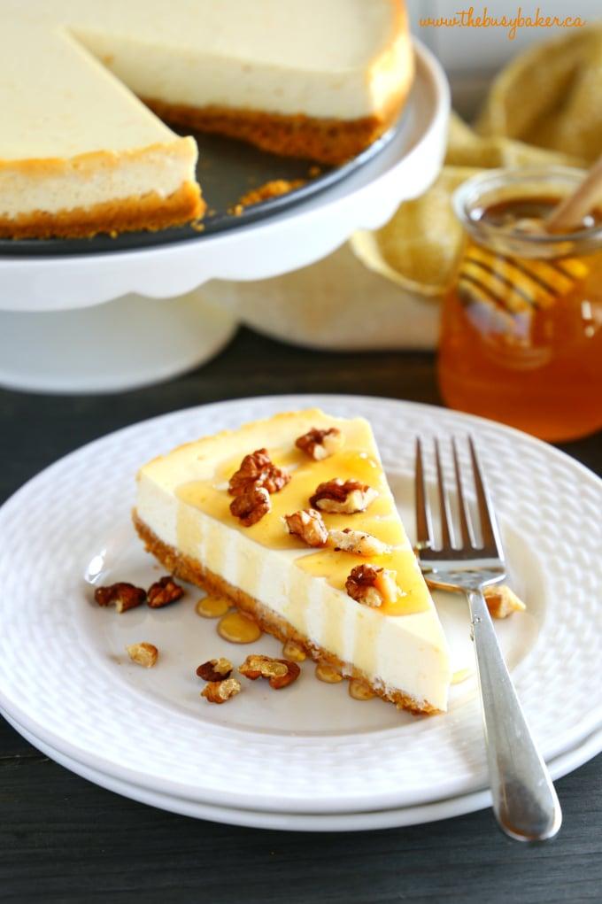 Healthy Honey Greek Yogurt Cheesecake on white plate with fork and honey