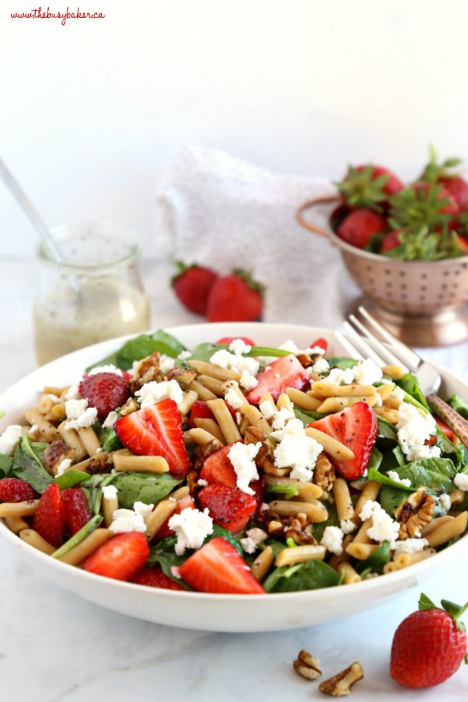 Strawberry Spinach Pasta Salad with Poppy Seed Dressing in white bowl with strawberries
