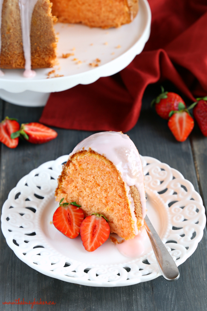 Best Ever Strawberry Pudding Cake on white plate with strawberries