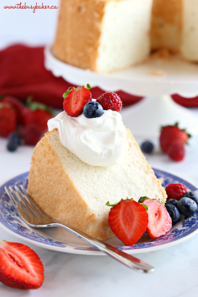 No Fail Homemade Angel Food Cake on plate with whipped cream and berries