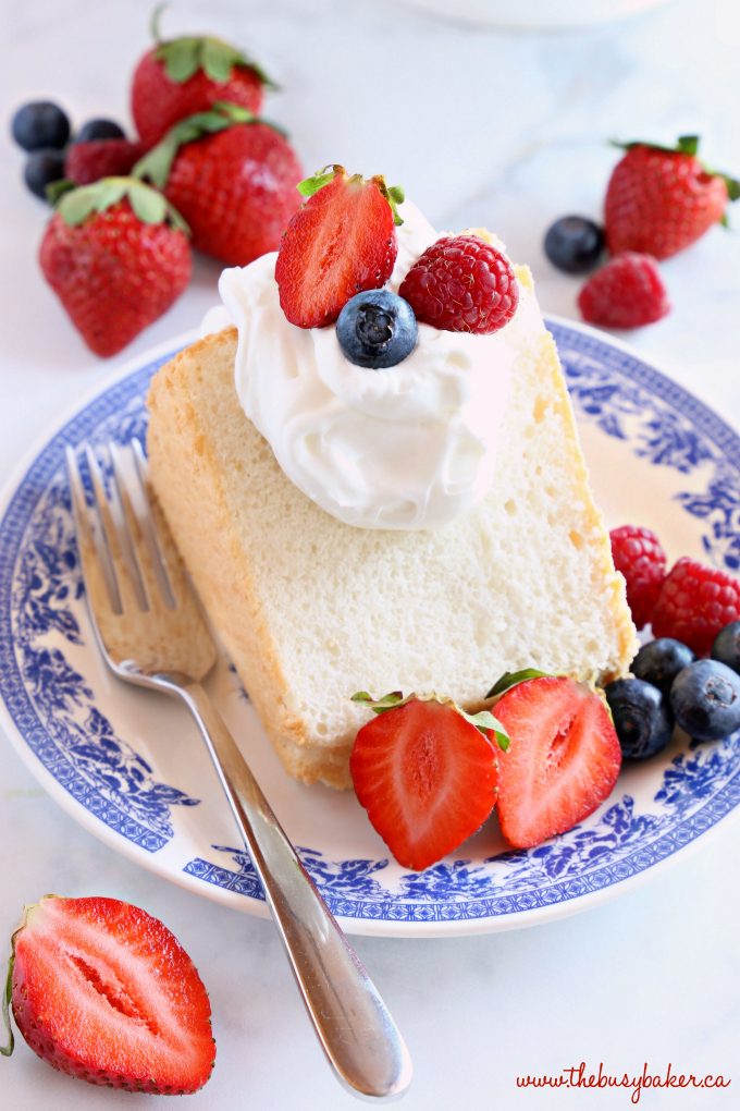 No Fail Homemade Angel Food Cake on blue vintage plate with fruit and whipped cream