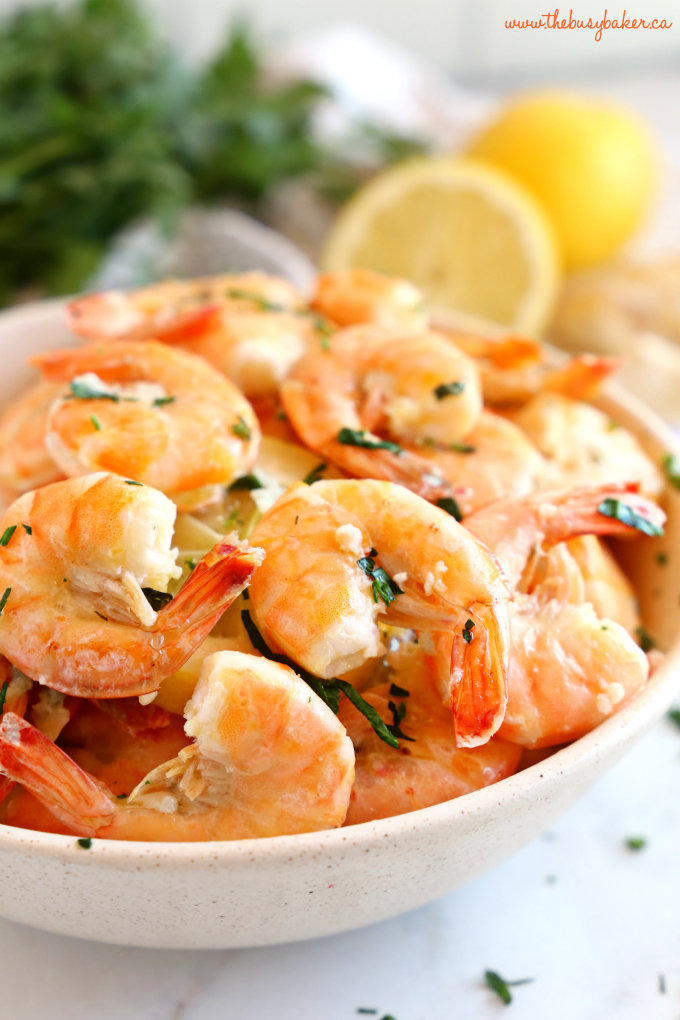 Easy Roasted Garlic Butter Shrimp in pottery bowl with lemon and herbs