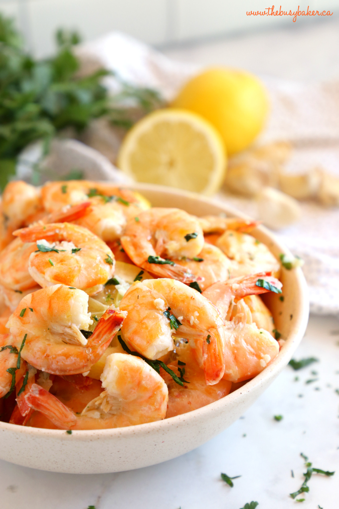 Easy Roasted Garlic Butter Shrimp in bowl with fresh garlic and herbs