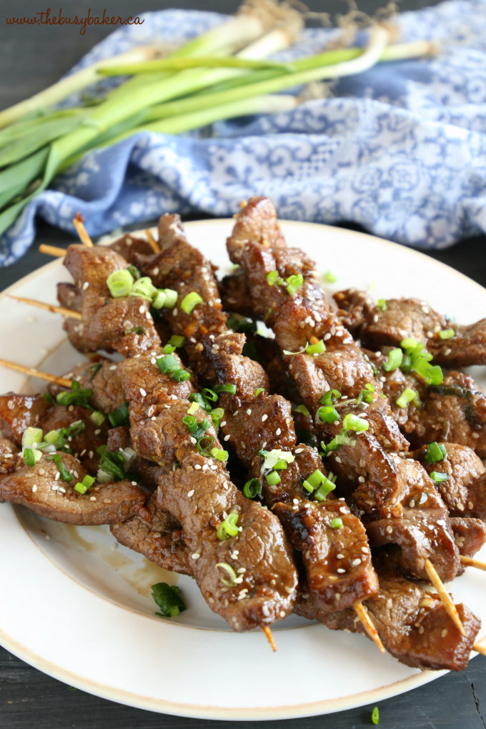 Best Ever Korean Barbecue Beef Skewers on white plate with green onions