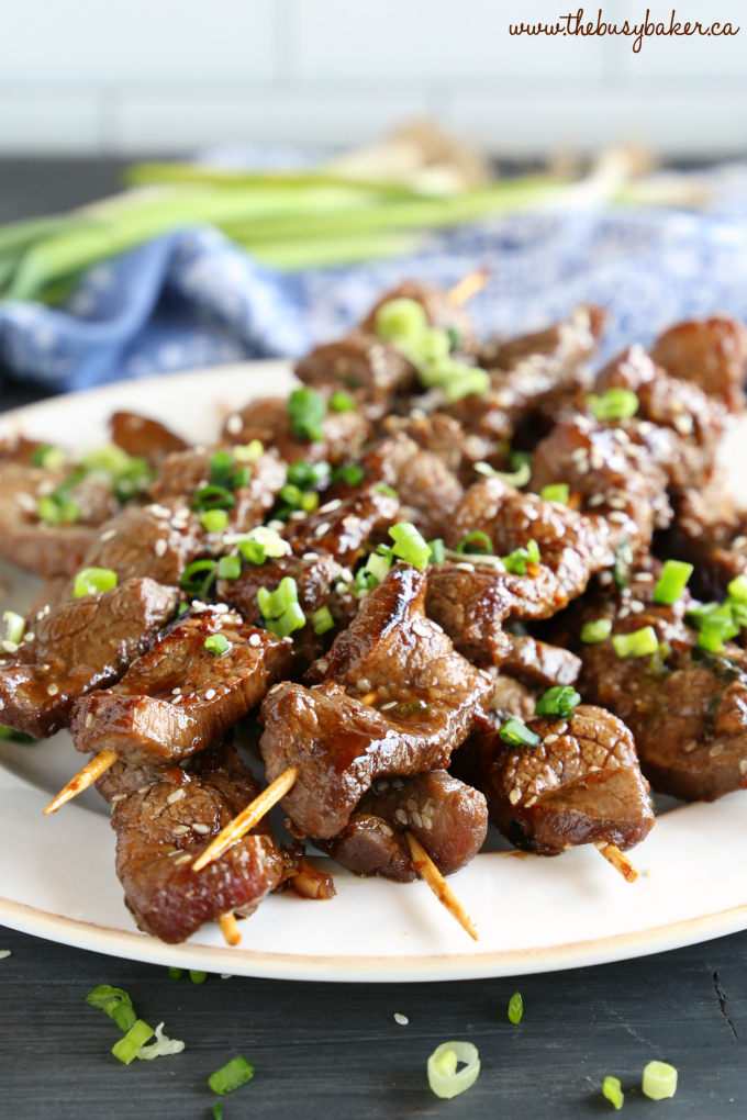 Best Ever Korean Barbecue Beef Skewers on plate with green onions and sesame seeds