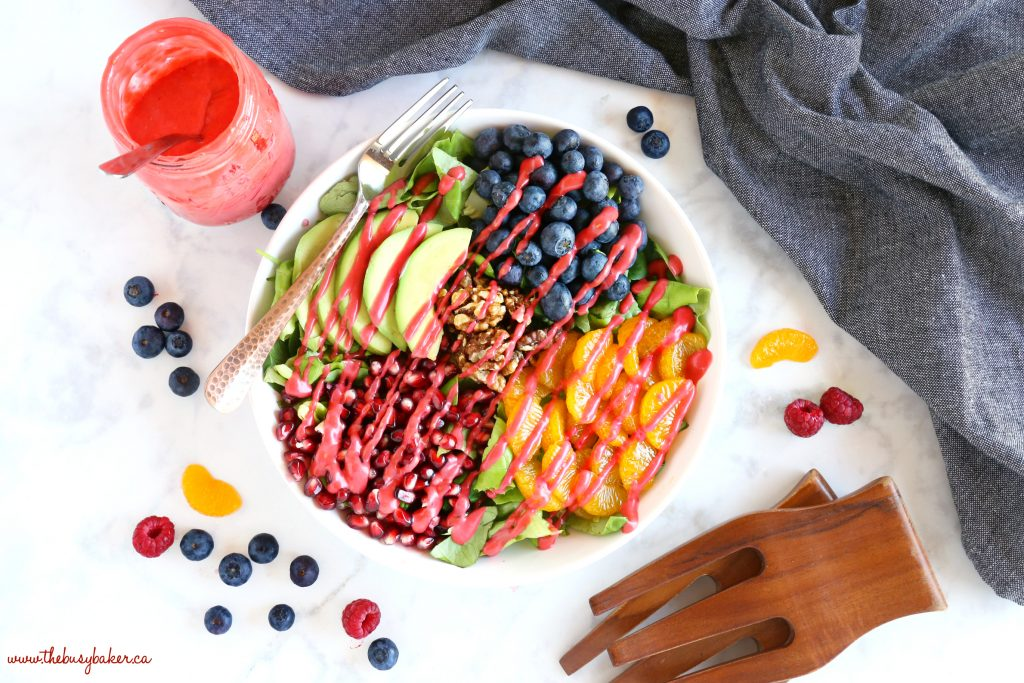 Orange Berry Pomegranate Superfood Salad with salad tongs and raspberry vinaigrette dressing