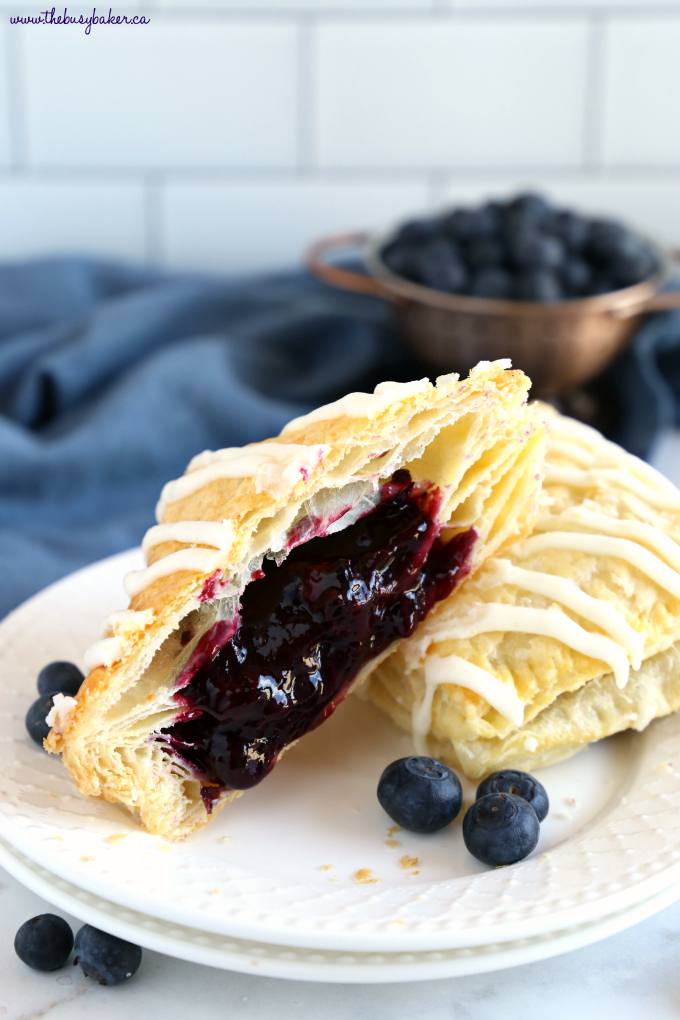 Best Ever Blueberry Hand Pies on white plate with blueberry filling and fresh blueberries