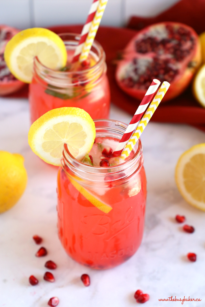 Healthy Pomegranate Lemonade in mason jar with paper straws and lemon slices