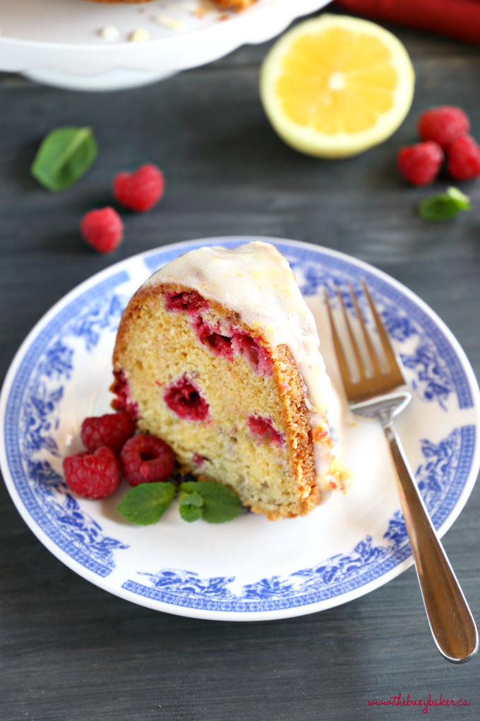 Lemon Raspberry Glazed Bundt Cake with blue vintage plate, fresh raspberries, and lemon slices