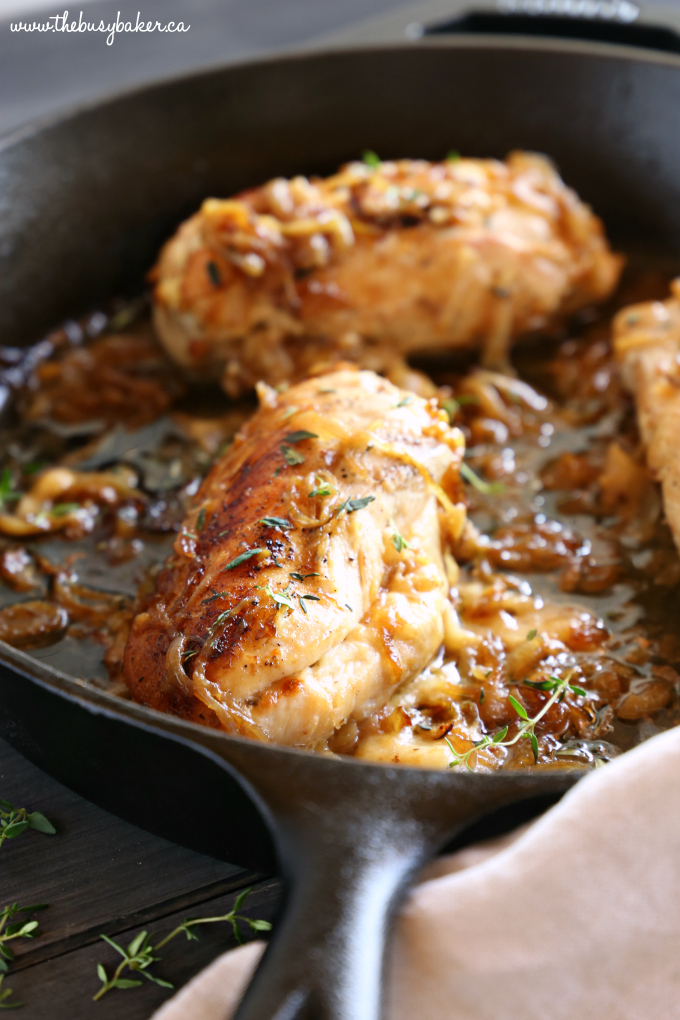 Easy One Pan French Onion Stuffed Chicken in cast iron skillet with fresh thyme