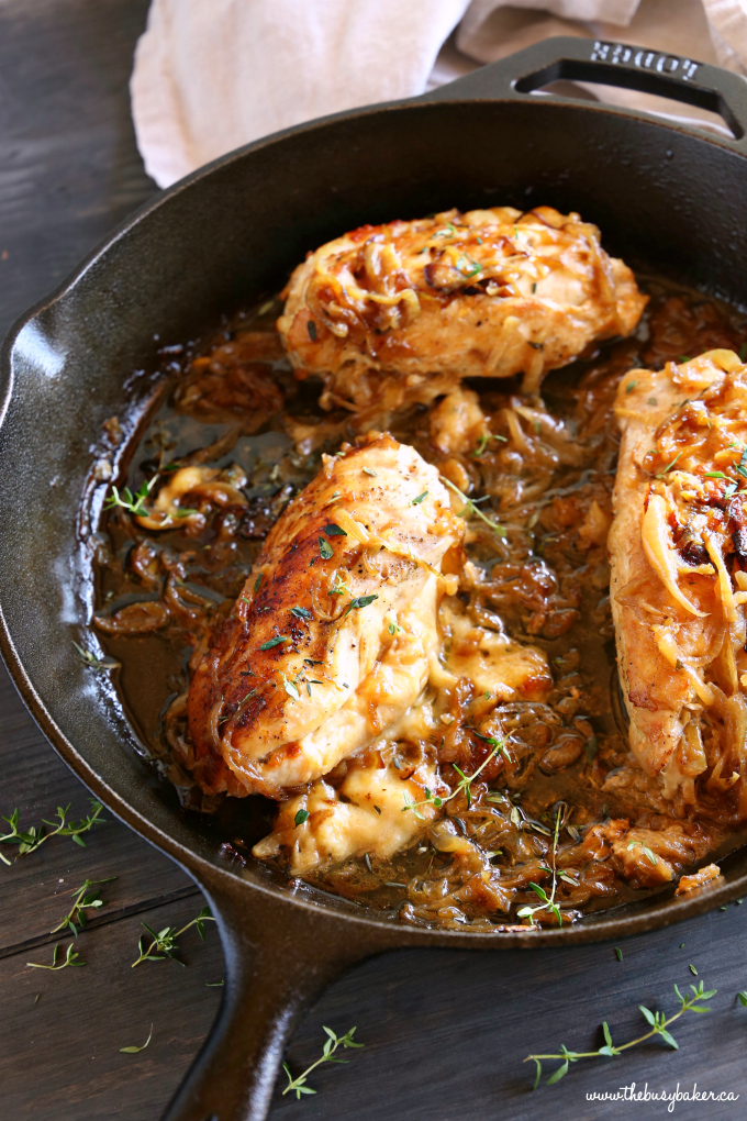 Easy One Pan French Onion Stuffed Chicken in cast iron skillet with caramelized onions and fresh thyme sprigs