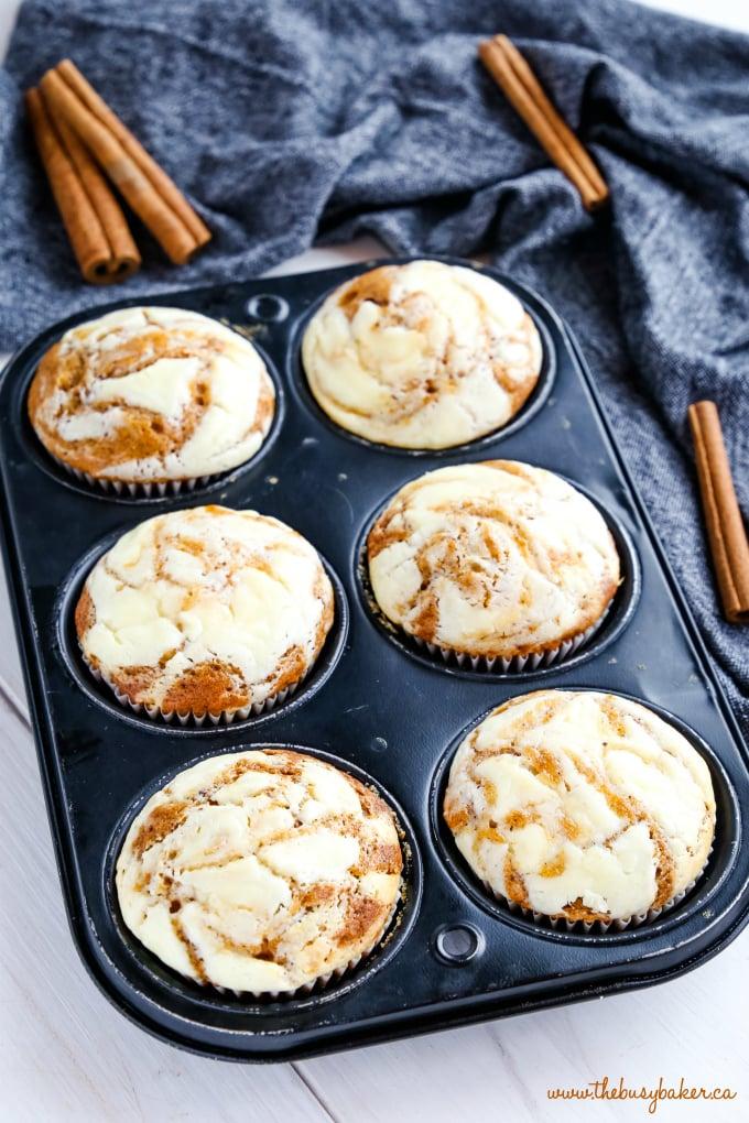 Pumpkin Cheesecake Swirl Muffins in muffin tin with cinnamon sticks