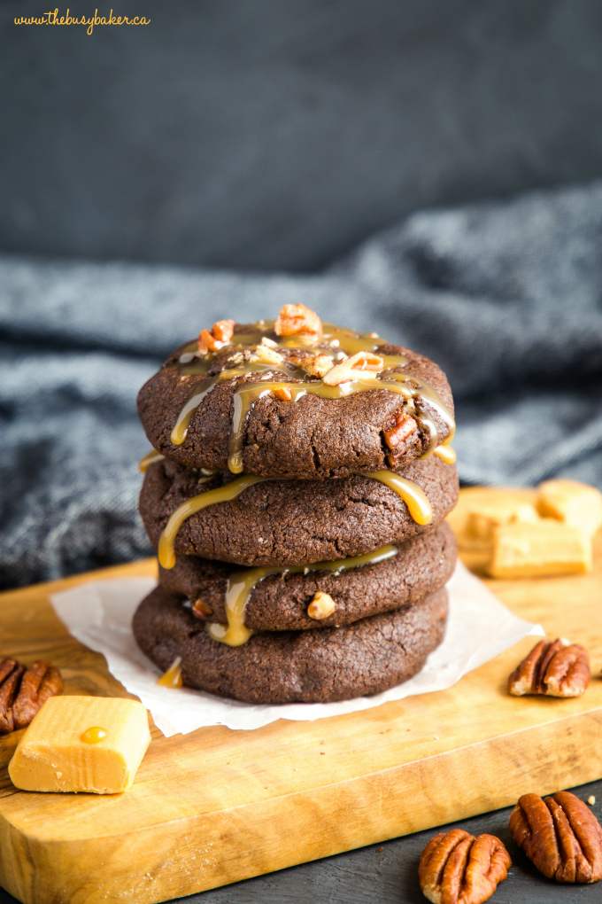 Chocolate Caramel Pecan Turtle Cookies in stack with caramel sauce