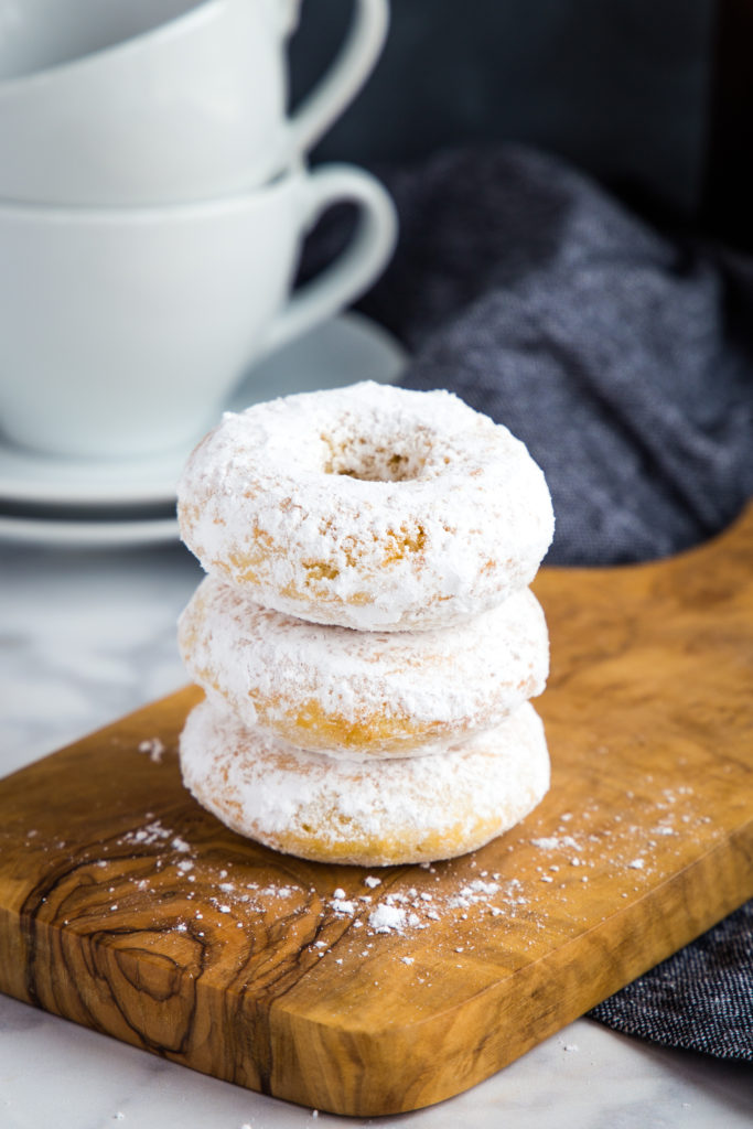 Old Fashioned Powdered Sugar Donuts in stack