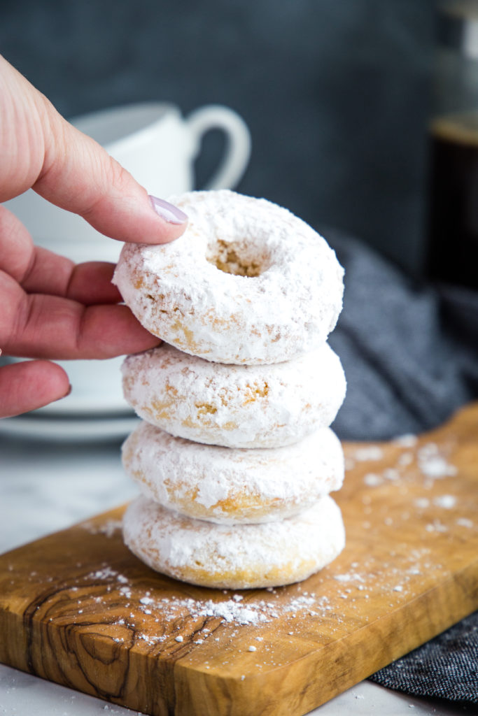 Old Fashioned Powdered Sugar Donuts in hand with coffee