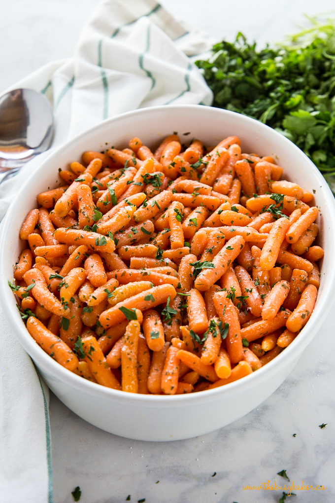 Garlic Butter Roasted Carrots in white oval baking dish with green parsley
