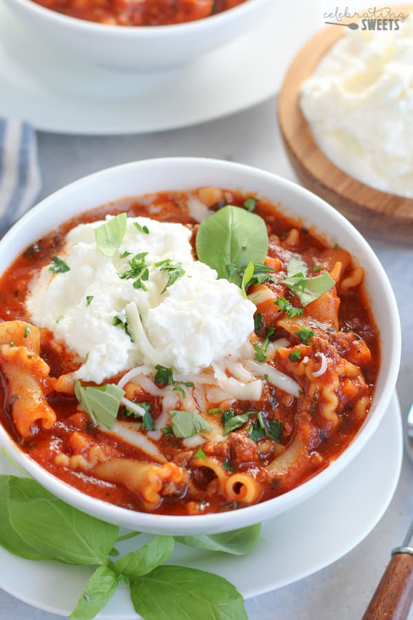 a bowl of lasagna soup topped with ricotta cheese