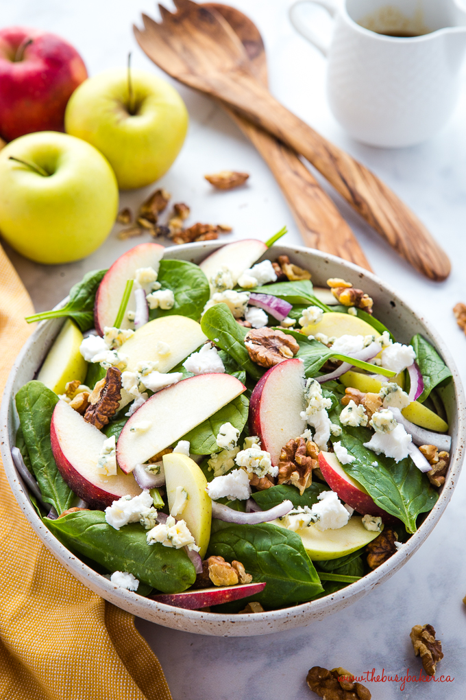 Apple Walnut Spinach Salad with Balsamic Vinaigrette in beige speckled pottery bowl with mustard yellow towel