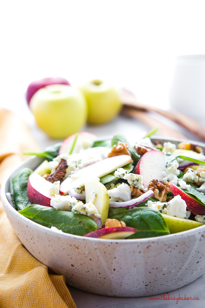 Apple Walnut Spinach Salad with Balsamic Vinaigrette in beige speckled pottery bowl